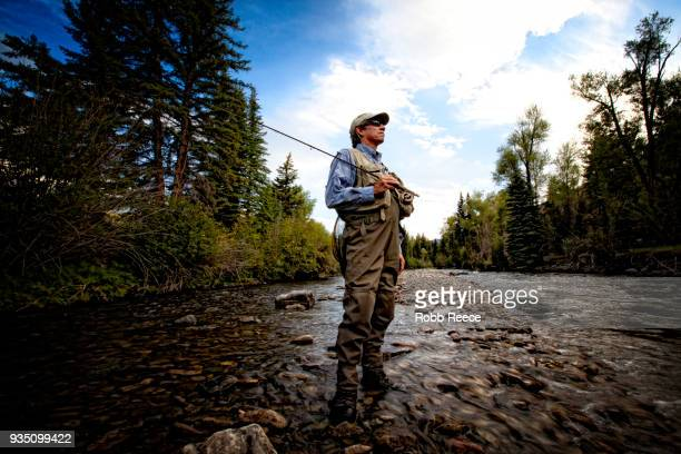 a male fly fisherman standing near a stream ready to fish - robb reece stockfoto's en -beelden