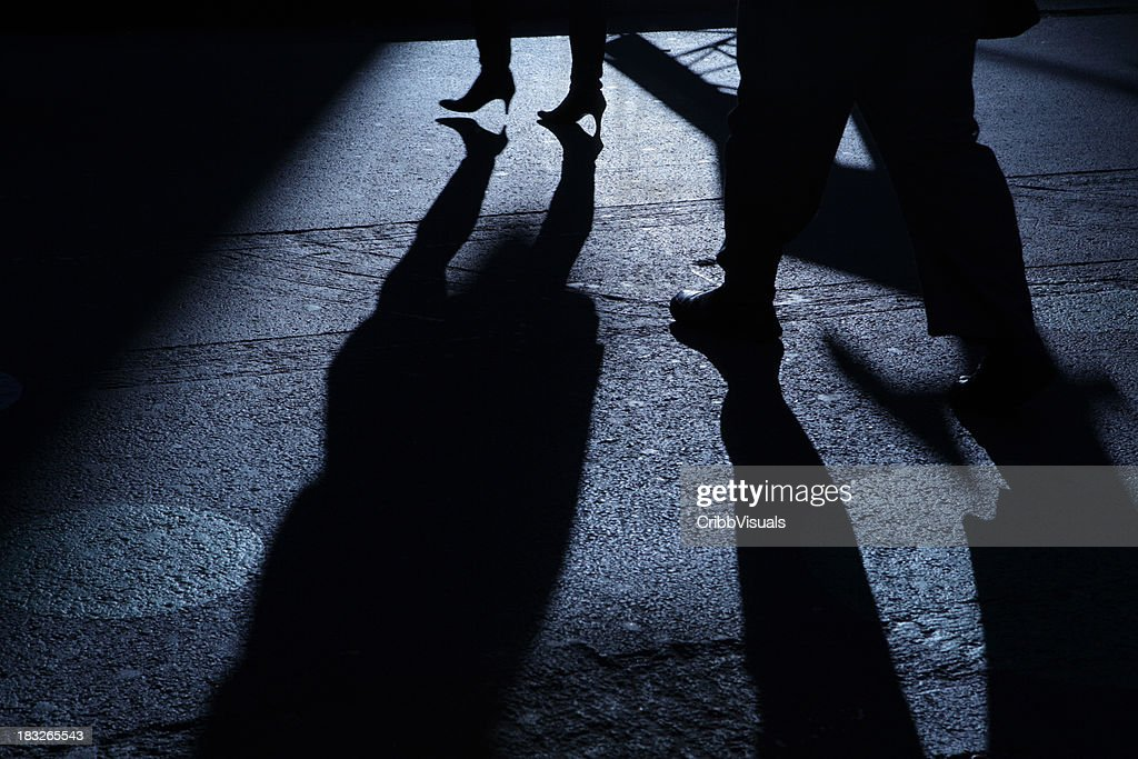 Male following female into blue night shadows : Stock Photo