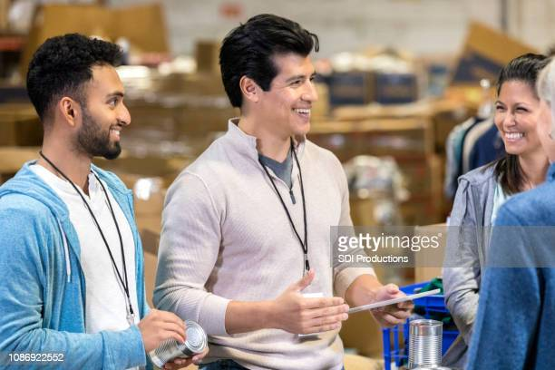 male food bank director talks with volunteers - non profit organization stock pictures, royalty-free photos & images
