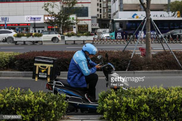 Male food delivery courier checks his phone in the street on on October 20, 2020 in Suzhou, China.