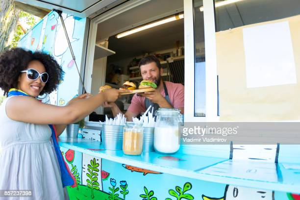 Male food van worker giving order to customer