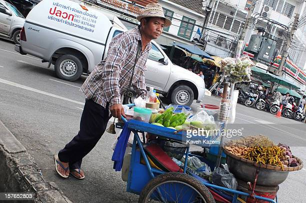 A male food vendor with a push cart seen on a busy street on October 25 2012 in Bangkok Thailand