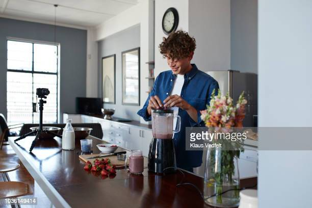 male food vlogger making video of blending a smoothie - haushaltsmaschine stock-fotos und bilder