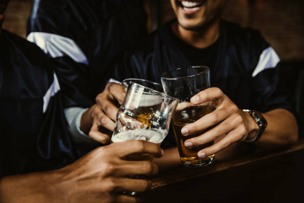male football fans toasting beer glasses in bar - drinking alcohol stock pictures, royalty-free photos & images