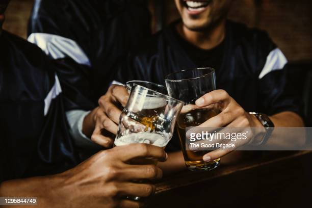 male football fans toasting beer glasses in bar - honour stock pictures, royalty-free photos & images