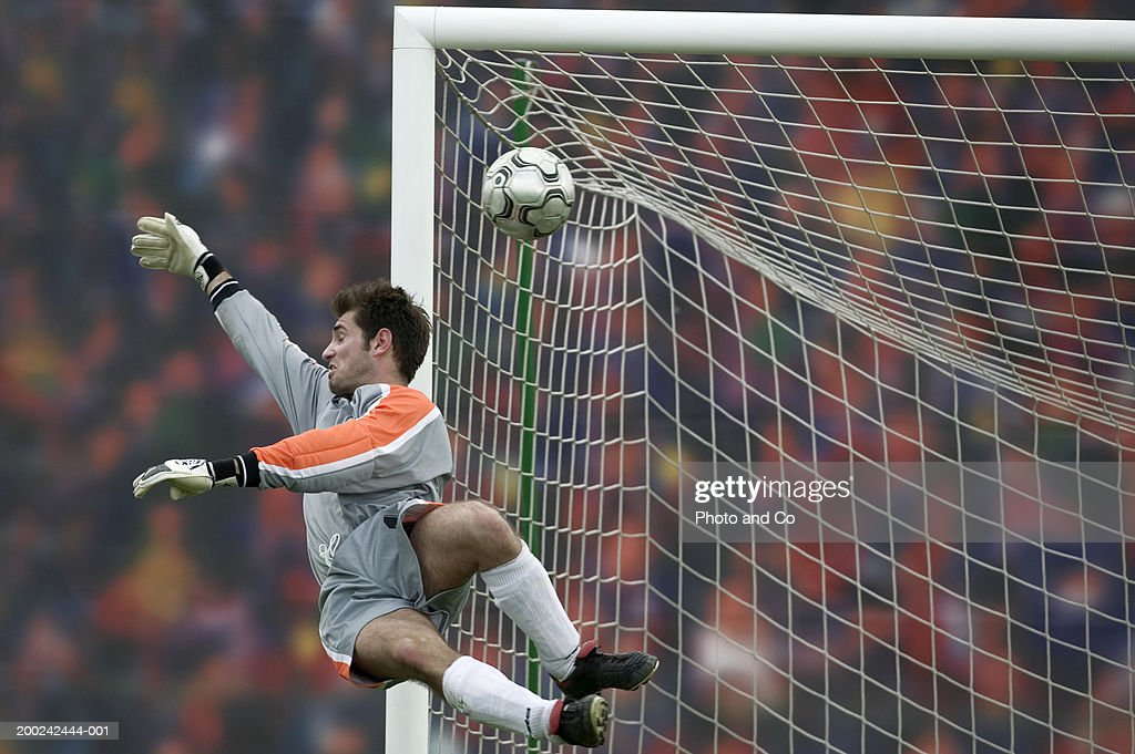 Male football goalie trying to block goal in air : Stock Photo