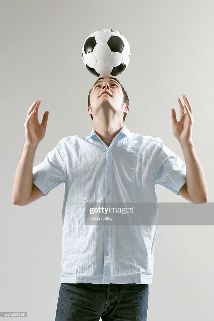 Male football player balancing ball on head : Stock Photo