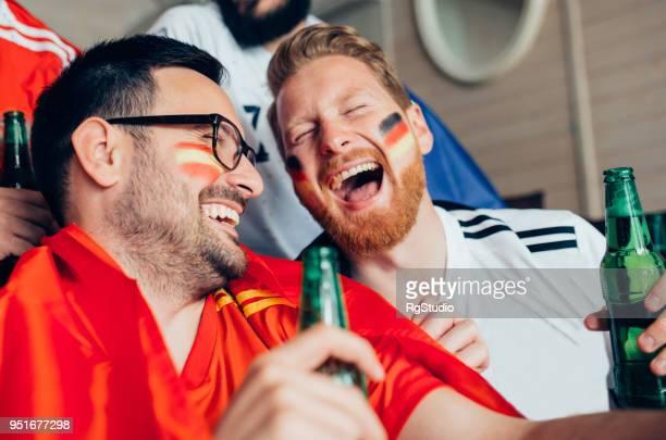 männlichen fußballfans bier trinken und lachen - weltmeisterschaft stock-fotos und bilder