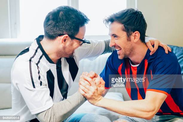 Male football supporters shaking hands