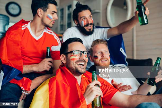 Fanáticos de fútbol masculino ver juego en TV y sonriendo