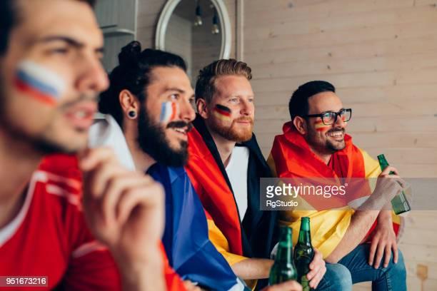 männlichen fußballfans mit gesichtsbemalung bier trinken und spiel im fernsehen beobachten - weltmeisterschaft stock-fotos und bilder