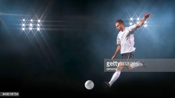 männlichen fußballer treten kugel - trefferversuch stock-fotos und bilder