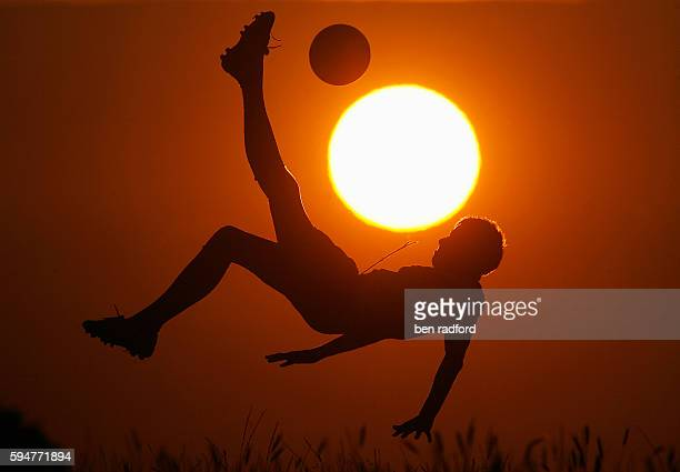 Male footballer performing overhead kick silhouetted against setting sun