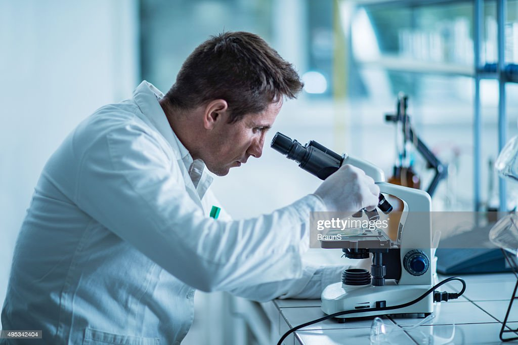 Male forensic scientist examining something through a microscope. : Stock Photo