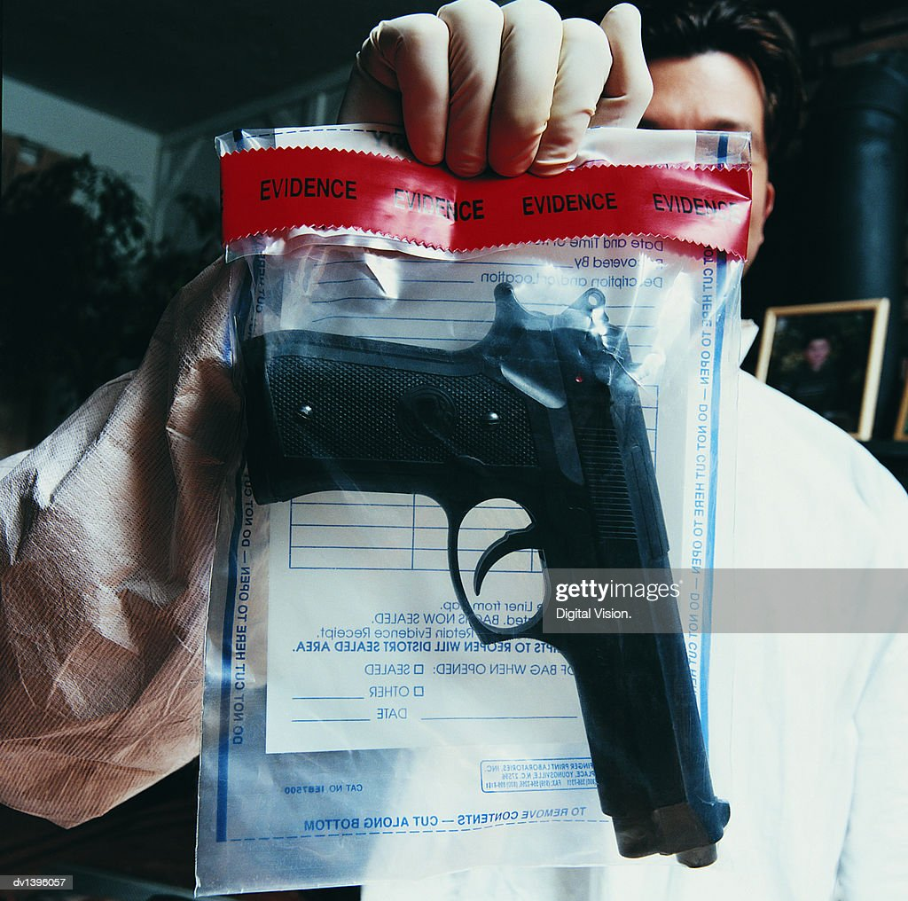Male Forensic Scientist Holding an Evidence Bag With a Gun Inside : Stock Photo