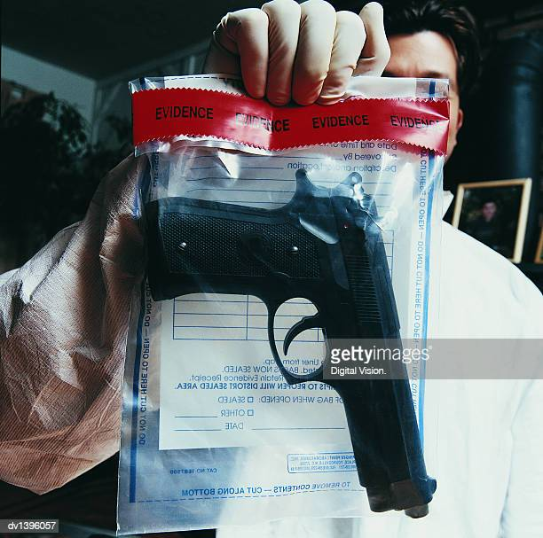 male forensic scientist holding an evidence bag with a gun inside - mord stock-fotos und bilder