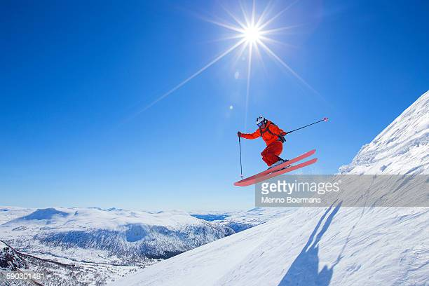 A male freerider in a red suit is jumping from a snow ridge. The sun is shining, the sky is blue.