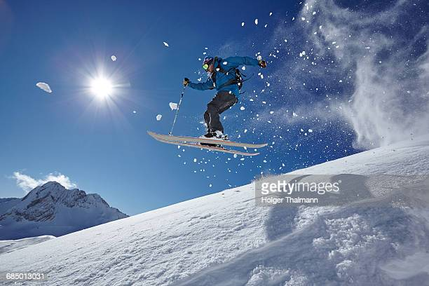 Male freestyle skier jumping mid air from mountainside, Zugspitze, Bayern, Germany