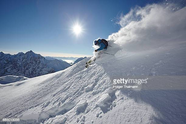 male freestyle skier skiing down snow powdered mountainside, zugspitze, bayern, germany - freestyle skiing stock pictures, royalty-free photos & images