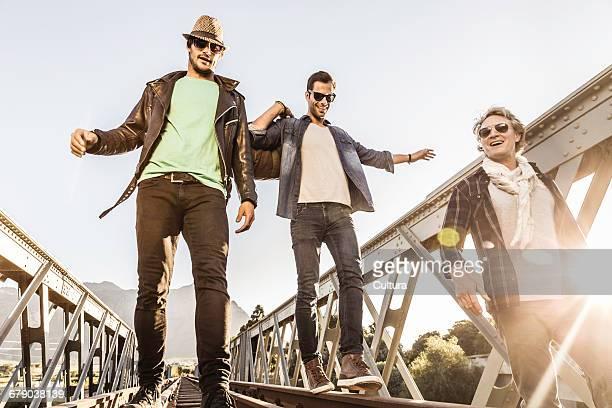 Male friends balancing on rural railway bridge tracks, Franschhoek, South Africa
