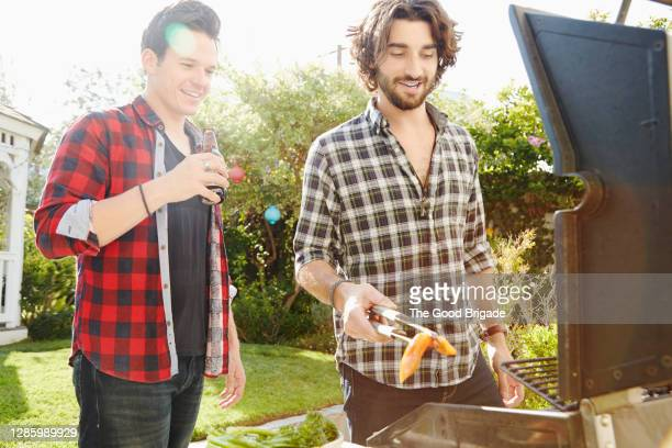 male friends barbecuing at backyard party - men friends beer outside stock pictures, royalty-free photos & images