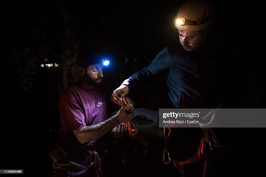 Male Friends Climbing Mountain At Night : Foto stock