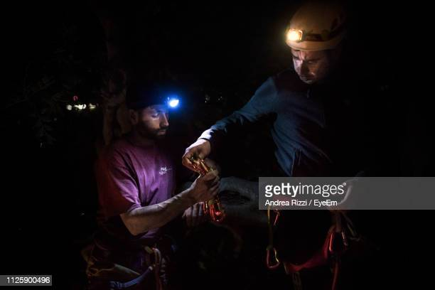 male friends climbing mountain at night - andrea rizzi fotografías e imágenes de stock