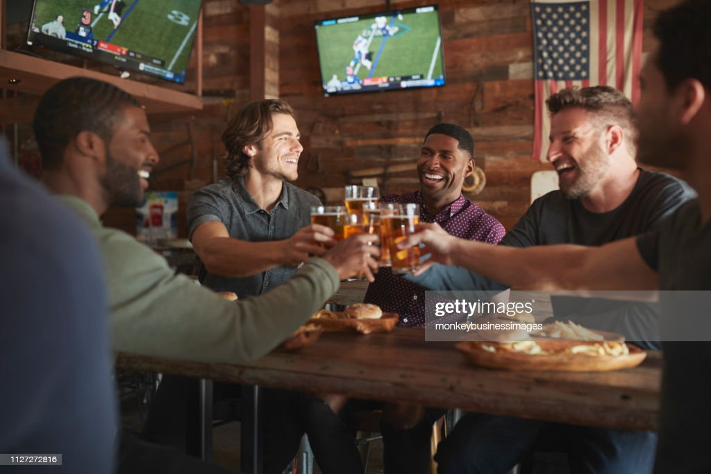 Male Friends Drinking Beer And Eating Burgers In Sports Bar : Stock Photo