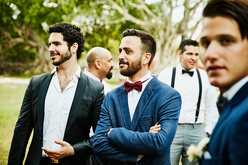 Male friends hanging out together during outdoor wedding reception - gettyimageskorea
