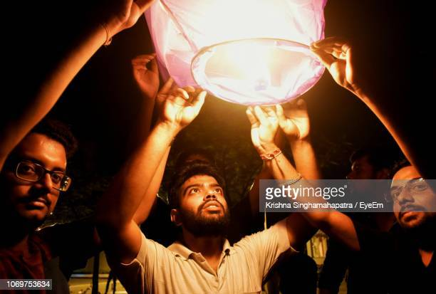 male friends holding lit paper lantern at night - south asia stock pictures, royalty-free photos & images