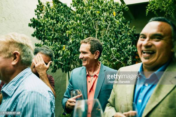 male friends laughing together during cocktail party - augen zuhalten stock-fotos und bilder