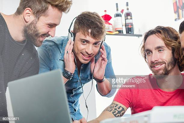 Male friends listening to music from laptop
