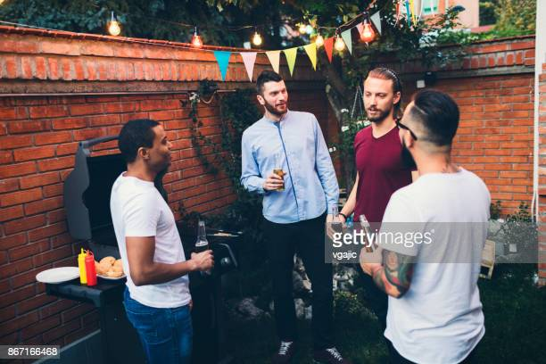 Male friends on a barbecue in back yard