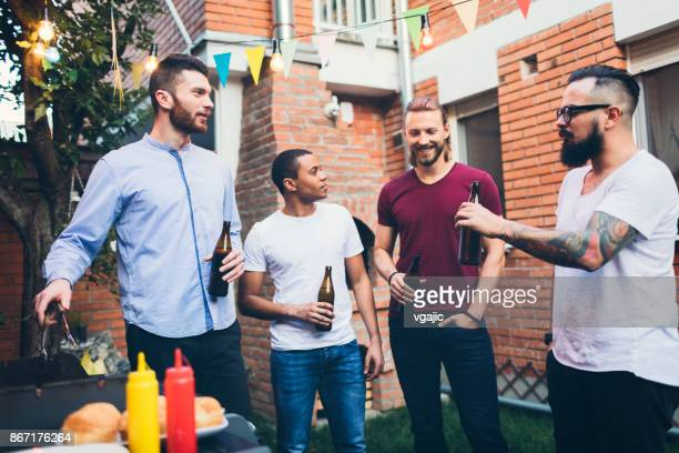 male friends on a barbecue in back yard - only men stock pictures, royalty-free photos & images