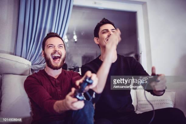 amigos homens jogando videogame juntos - irmão - fotografias e filmes do acervo