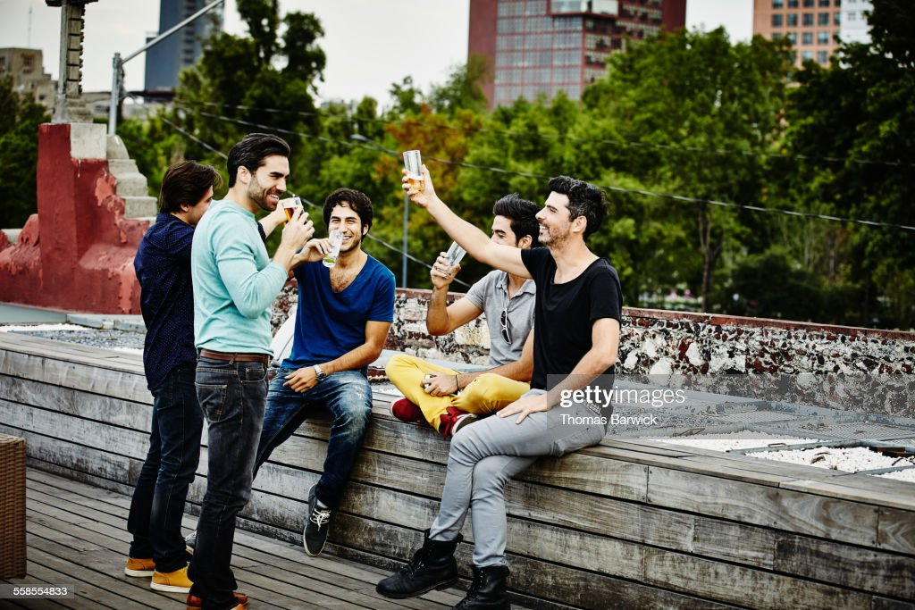 Male friends raising glasses to toast during party : Stock Photo