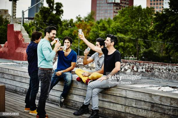 Male friends raising glasses to toast during party