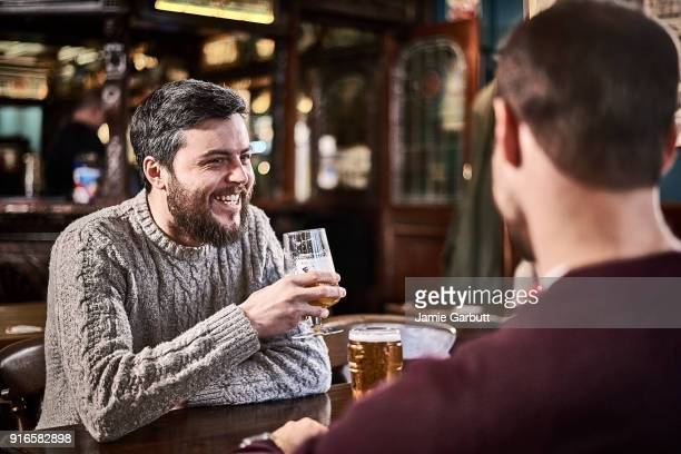 male friends sat in a british pub laughing and drinking together - ale stock pictures, royalty-free photos & images
