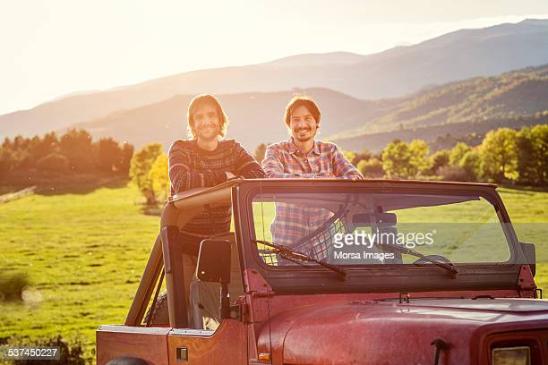Male friends standing in jeep at field