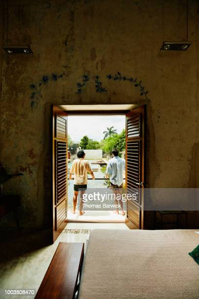 Male friends standing on balcony of room at luxury resort overlooking courtyard pool