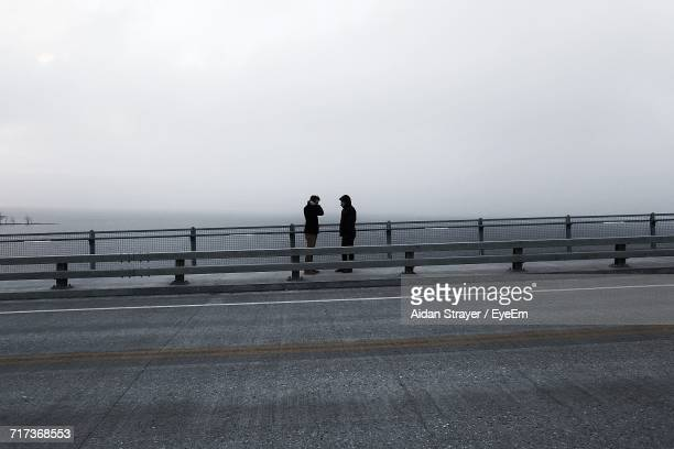 Male Friends Standing On Promenade By Sea During Foggy Weather