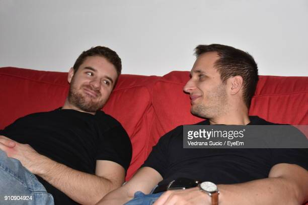 Male Friends Talking While Relaxing On Sofa At Home