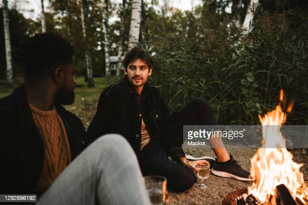 male friends talking while sitting by fire pit during weekend - sweden stock pictures, royalty-free photos & images