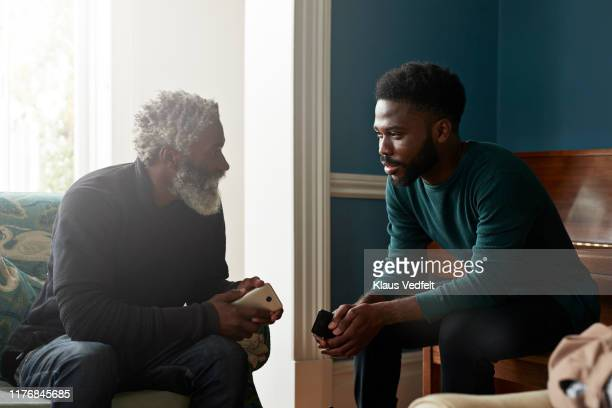 male friends talking while sitting in living room - two generation family stock pictures, royalty-free photos & images
