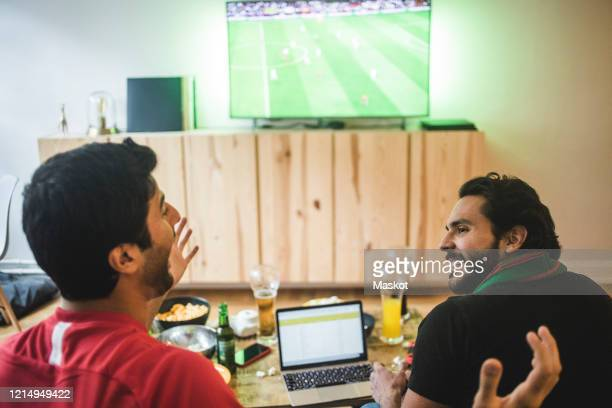 male friends talking while watching soccer in living room - fan enthusiast stock pictures, royalty-free photos & images