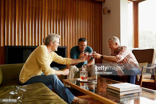 male friends toasting alcohol glasses at home - whisky photos et images de collection
