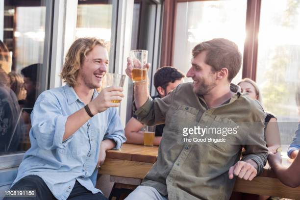 male friends toasting beer glasses at pub - men friends beer outside stock pictures, royalty-free photos & images