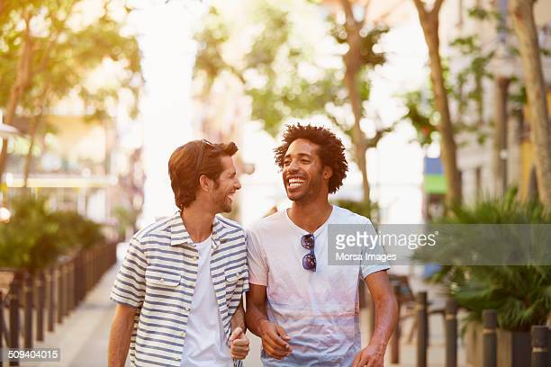 male friends walking outdoors - male friendship stock pictures, royalty-free photos & images