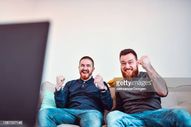 male friends watching intense sports match - fan enthusiast stock pictures, royalty-free photos & images