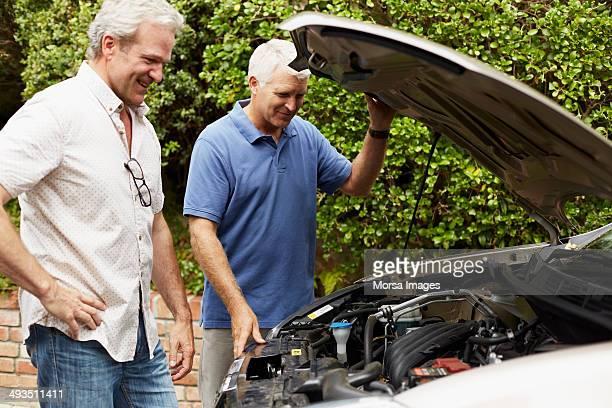 Male friends with broken down car on street